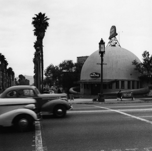 "memoriastoica:  Cars speed down Wilshire Boulevard, where it crosses S. Alexandria Avenue right outside The Brown Derby Restaurant. An original ""Wilshire Lantern"" street light is seen on the corner. Photographer: Ansel Adams Circa 1940."