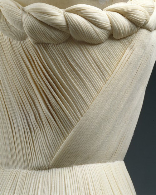 fashioninhistory:  Evening Dress (detail) Madame Grès 1958 Grès, working earlier as Alix, created dresses in shafts of fabric, the diverse fluting of which served on the body like the entasis of a classical column. Seaming together fabric vertically so as to be continuous from hem to neckline, Grès pleated and tucked the materials into a shaping suitable to the body: the same fabric is buoyant and fluid when release-pleated from the waist down. She simulated a waist seam by tight tucking that continues through the bodice, and crowned the dress with volutes and twists. This tour-de-force of material rendered in diverse ways accounts for the tempered ergonomics of such dresses. Their wearers have testified that they felt secure and not immodest in these dresses, so organic was their creation. In this example, only one piece of fabric was added to the column: a small triangle was inserted under the arm to complete the structure, but otherwise the entire dress is conceived as one cylinder.