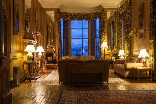 The drawing room of the Ardanaiseig Hotel with a snow capped Ben Lui in the distance. Ardanaiseig, Scotland.