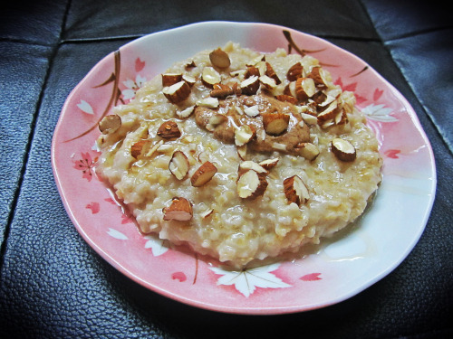 Oatmeal with brown sugar topped with almond butter, chopped almonds, and drizzled with honey.