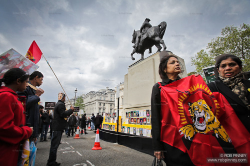 robpinney:  London, United Kingdom. May 18th, 2013.  Tamil protesters gather around photographs of those killed during the Sri Lankan civil war.  Thousands of Tamils march through central London to commemorate those killed during the final stages of the Sri Lankan civil war and to call on Prime Minister David Cameron to boycott the Commonwealth Heads of Government Meeting, to be held on Colombo in November 2013. (© Rob Pinney / www.robpinney.com)