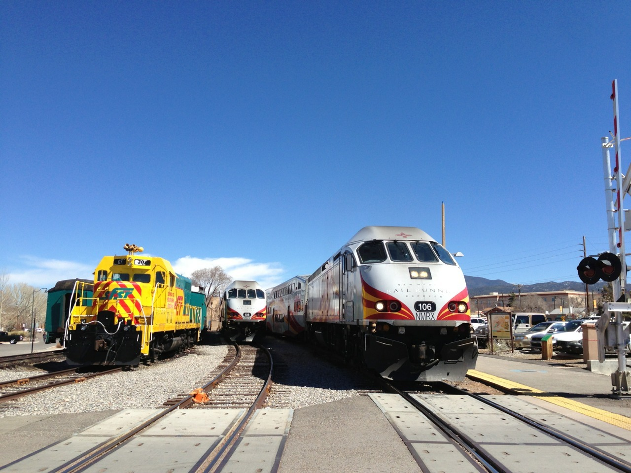 A couple of New Mexico Rail Runners and a Santa Fe Southern Railway sitting at the Santa Fe Rail Runner Station.