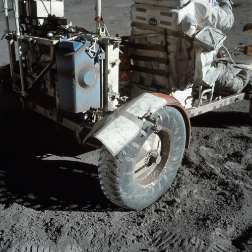 AS17-137-20979 (12 Dec. 1972) —- A close-up view of the lunar roving vehicle (LRV) at the Taurus-Littrow landing site photographed during Apollo 17 lunar surface extravehicular activity. Note the makeshift repair arrangement on the right rear fender of the LRV. During EVA-1 a hammer got underneath the fender and a part of it was knocked off. Astronauts Eugene A. Cernan and Harrison H. Schmitt were reporting a problem with lunar dust because of the damage fender. Following a suggestion from astronaut John W. Young in the Mission Control Center at Houston the crewmen repaired the fender early in EVA-2 using lunar maps and clamps from the optical alignment telescope lamp. Schmitt is seated in the rover. Cernan took this picture.