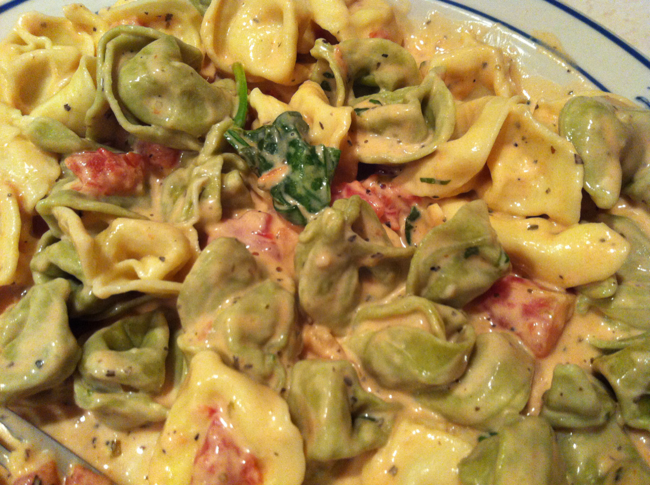 Tortellini with Spinach in a Tomato Cream Sauce. Difficulty: * This sauce has so much flavor… it is so incredibly delicious and I couldn't believe how easy it was to make.  I copied the recipe exactly from here: http://allrecipes.com/recipe/spinach-tomato-tortellini/detail.aspx Ingredients - 1 large package of tortellini.  I bought a 20 oz package of tortellini and still had leftover sauce, but that's ok because you can jar it and freeze it to reuse. - 1 can diced tomatoes with italian seasoning - 1 cup chopped fresh spinach - 1/2 tsp salt - 1/4 tsp pepper - 1 1/2 tsp dried basil - 1 tsp minced garlic (this was 2 cloves for me) - 2 tbsp flour - 3/4 cup milk - 3/4 cup heavy whipping cream - 1/4 cup grated parmesan cheese Recipe 1. Boil water and cook tortellini according to directions on package while you're preparing the sauce 2. In a saucepan combine tomatoes, spinach, salt, pepper, basil and garlic.  Stir until bubbly 3. In a separate bowl, whisk together flour, milk and heavy cream.  Stir into your tomato mixture.  I have a feeling it would be fine to slowly whisk these into the pan directly. 4. Stir in the parmesan cheese. 5. Reduce heat to low and simmer until thick, about 2 min. 6. Serve and enjoy! Seriously Eatsy: The Not-Your-Average-Cooking-Blog Blog