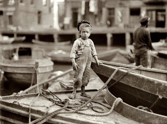 Truant hanging around boats in the harbor during school hours, Boston, 1909, by Lewis Hine
