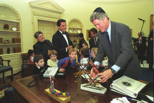 Celebrating Hanukkah in the Oval Office President Bill Clinton and children from the Jewish Community Center in Washington D.C. light a menorah in the Oval Office.  December 8, 1993. -from the Clinton Library