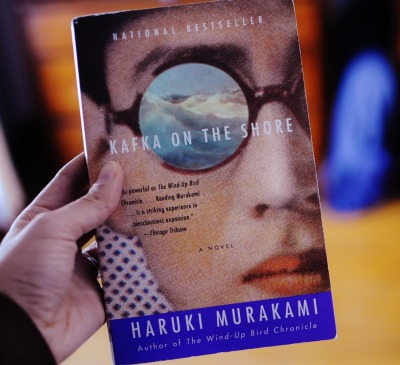 Kafka On the Shore By Haruki Murakami (No Spoilers) Quick Review 3.5 stars out of 5 Sigmund Freud believed our dreams held our repressed unconscious thoughts. Murakami's book, Kafka on the Shore, takes this idea and takes it beyond fantasy. The entire book almost felt like a never ending dream sequence and a dream within a dream. The story centers around a 15 year old boy named Kafka who runs away from home to escape a curse. The chapters alternates between Kafka's story and another story about a mysterious occurrence in a forest(sorry don't want to spoil). The book is a page turner up until three quarters of it. Afterwards, it becomes incoherent and seems to be going nowhere. My main gripe about the book is it almost felt like the entire thing was improvised. The beginning chapters were gripping and filled with mystery and suspense then we are introduced to useless characters named after KFC's founder, Colonel Sanders. Sure, I could be missing the entire point. Murakami said the book is filled with riddles the reader has to interpret. However, I just became so uninterested in the story that I didn't even care about solving it. I just wanted to finish. I also didn't like the fact that Murakami had to keep pointing out which Greek story, philosopher, book, etc the story was mirroring. He doesn't seem to have much faith in his reader's knowledge. Still, the book is translated beautifully. The style and prose poetic. Storytelling is mesmerizing and makes me curious to read Murakami's The Wind-Up Bird Chronicles, IQ84, and Norwegian Wood. Those three books seem to be his more critically acclaimed books.