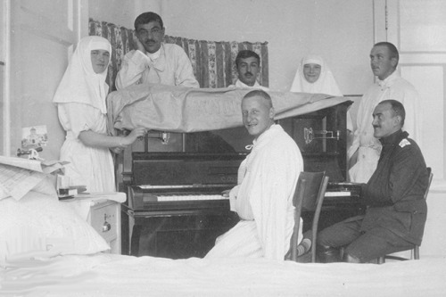 Grand Duchesses Olga and Tatiana at the piano with some wounded officers from the lazaret: c. 1915.