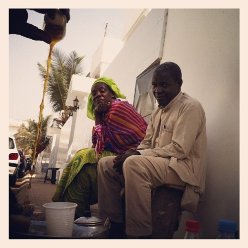 "Khady, left, and Ibrahima, right, watch Pape as he prepares ""ataya"" or tea in Dakar, Senegal.  Taking ataya is a tradition in west Africa where friends come together multiple times a day to socialize as one person pours tea from one small glass to another to mix the ingredients and create a foam before drinking. Photo by Jane Hahn @janehahn #senegal #dakar #teatime #ataya #friends"