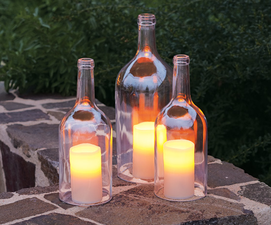 Bottled Outdoor Candle Lighting  What an efficient way to recycle your whine bottles? They will protect candle flames from any wind condition and make it a lot more interesting to look at.