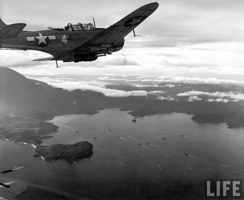 SBD Dauntless Dive bomber over Tanahmerah Bay, Pacific theatre.