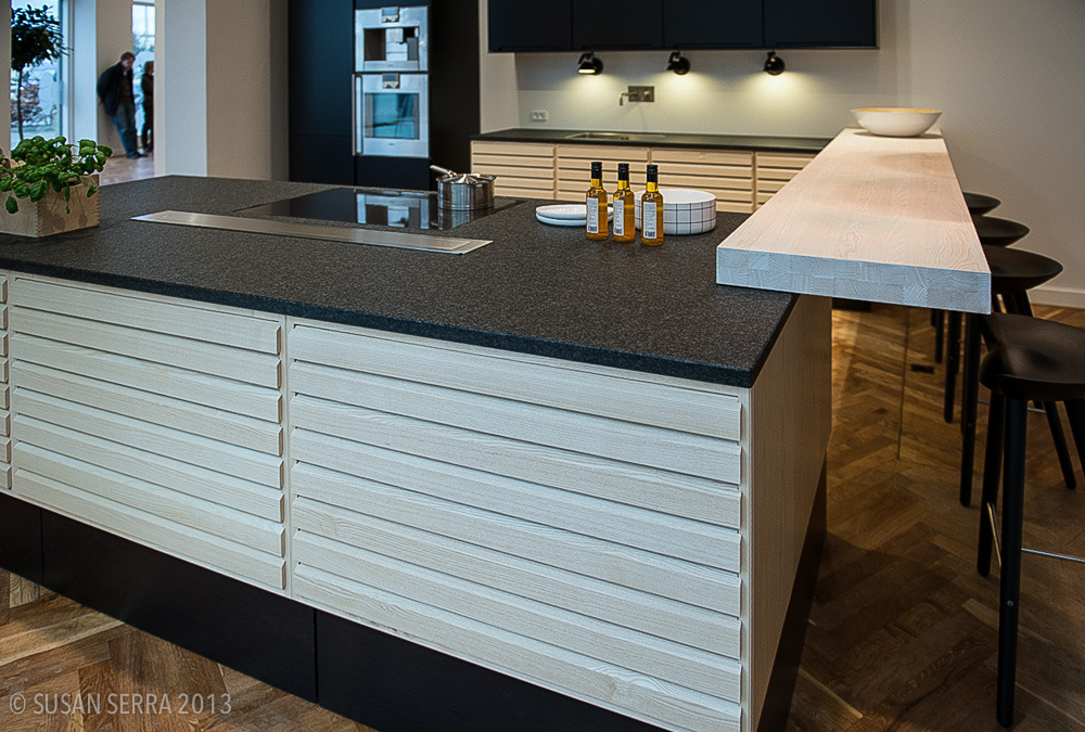 This kitchen in the Uno Form showroom in Copenhagen features the warmth of wood combined with cool neutrals. The rustic yet classic flooring adds a needed cozy factor. The pattern of the cabinetry adds interest to the long pieces.