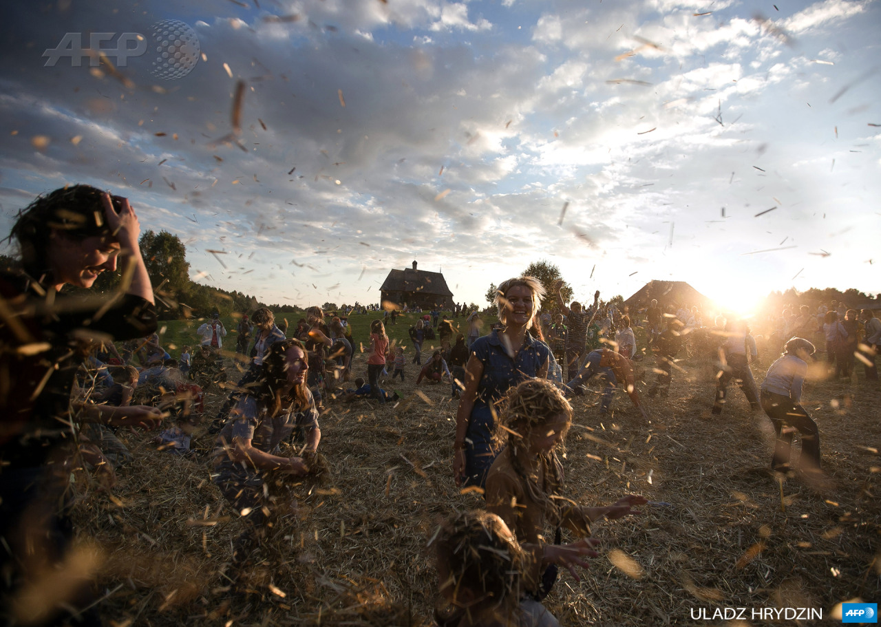 BELARUS, Minsk: People dance and throw straw during a traditionnal festival in village Ozerco, some 10km from Minsk, on September 6, 2014. AFP PHOTO / ULADZ HRYDZIN