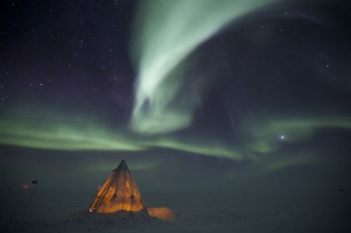 invocates:  A Scott tent set up at the Geographic South Pole, Antarctica. Set up outside the Amundsen-Scott South Pole Station. A 30-second exposure of an aurora over the tent used for camping during the winter of 2009. Campers overnight here in order to get out of the station and sleep at -80ºF. (Via NationalGeographic)