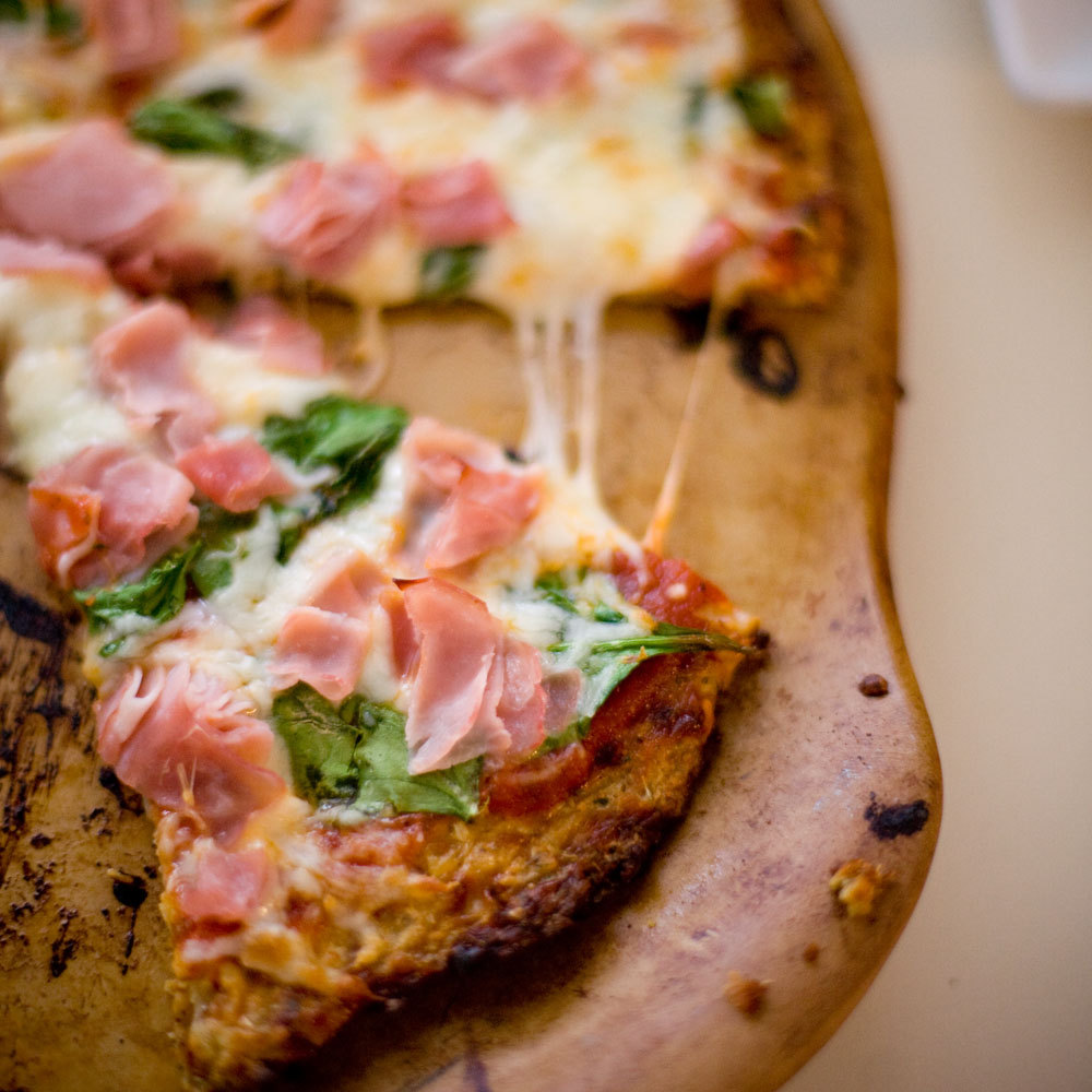 gluten-free cauliflower pizza crust with ham, cheese, and spinach.