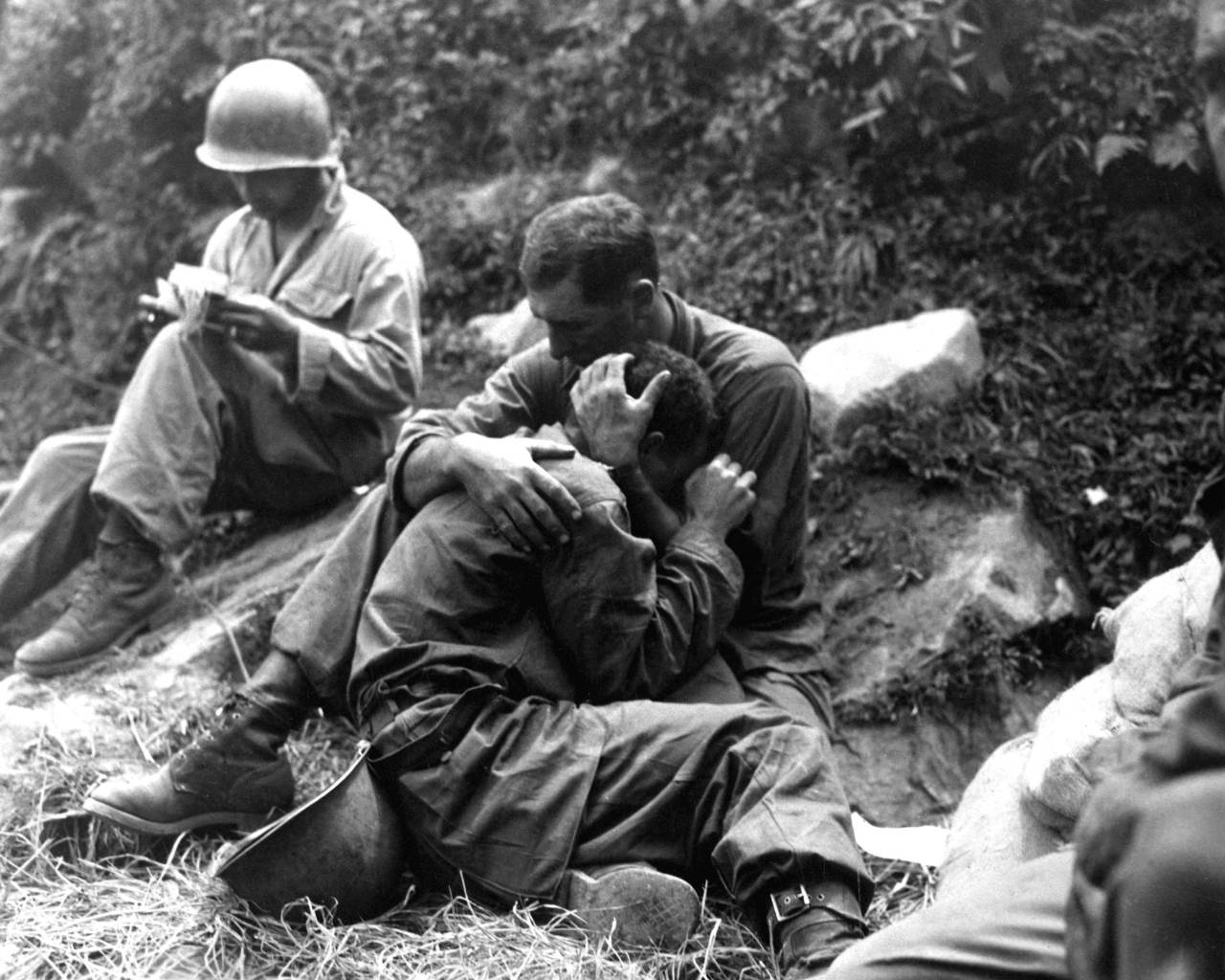 collectivehistory:  A grief stricken American infantryman being comforted by another soldier. In the background a corpsman methodically fills out casualty tags, Haktong-ni area, Korea. August 28, 1950