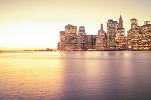 "New York City. The skyline at sunset. Financial District. New York City is magical  during the pause between night and day  when the sun dips behind the skyline  shining its light out through the twinkling eyes of the buildings.  This time of day is when   dreams roll off the tongue,   with a slow-motion exhale   at the end of a word  in a phrase  that trails off  without end.—-Winter in New York City isn't the friendliest especially near the water when the wind-chills dip into the single digits and the wind whips across the waves. This is the result of a 30 second long exposure taken last night with the Sony a99 after a long-walk over the Brooklyn Bridge. The view is of the skyscrapers of the Financial District in lower Manhattan and the Statue of Liberty can be seen fading into the sun-streaked horizon. I have always loved the way the skyscrapers in this view just sort of abruptly break up the more open view on the left. I love the moments just after sunset. The sky sinks into a momentary pause before the night sky pulls itself over the city. When everything is devoid of color on cloudy days, the tiny bits of color during these moments that come from the lights in the skyscrapers and the color that streaks across the bone-chilled-grey sky reach right into the heart. —-View this photo with a comment thread on my Google Plus page—-Buy ""New York City Skyline at Sunset - Lower Manhattan Skyscrapers"" Posters and Prints here, email me, or ask for help."