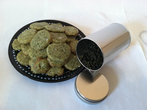 "Milk Oolong Tea Cookies Ingredients:2 cups flour6 T milk oolong2 pinches salt1 cup butter, softened (just leave it out overnight)1/2 cup confectioner's sugar1 dash almond extract (I bet vanilla would do brilliantly as well) Halved almonds or halved walnuts for Garnish Directions:Grind the milk oolong with a mortar and pestle. Sift the twigs and stems and larger pieces away from the powder and dispose of. Repeat process until you have something akin to a Matcha powder, only with Oolong. Mix the faux matcha, flour, and salt in the smaller mixing bowl.Mix butter, sugar, and splash of almond extract in the larger bowl. Now mix them more. And more. Make this as soft and homogeneous as you can. Add the flour mix to the butter mix, bit by bit. Divide in two. Place one half on the wax paper. Holding the ends of the paper up, roll the dough around a bit to convince it to look like a vaguely-cylindrical log, aiming for a log about 2"" in diameter. Fold the paper over the log and close the ends, kinda like a candy wrapper. Repeat process for other half of the dough batch. Place the logs on a small tray and freeze for about an hour (no longer). Preheat your oven to 350F. Take the logs out of the freezer, cut them into slices between 1/4in and 1/2in. Lay them out on an ungreased pan (or two), about 1/2in to 1in apart. If you want to put halved almonds or something atop them before baking, now's your time! Bake for 10-15 minutes. Watch them closely! You don't want them to actually change color, only to get kinda golden around the edges. Remove from oven, allow to cool, then eat."
