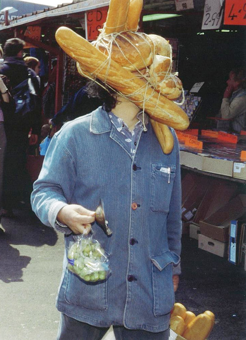 vagabondedlife:   Bread Man, 2001 by Tatsumi Orimoto  On 8 May 2001, Tasumi Orimoto made a performance as his famous alter ego 'Bread Man', his face obscured behind a tangle of twine and loaves of bread. The artist believes that what matters above all is the effect he has on the people he encounters. Deliberately, he was barely able to see through his self-imposed deformity as he walked around the open market shaking hands and announcing his presence by ringing a small bell. The overall mood engendered by the performance was one of strange camaraderie.