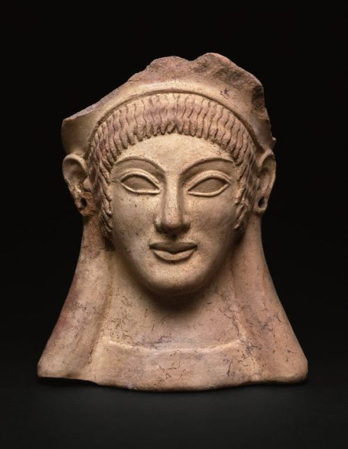 Votive Head c. 500 BC Etruscan  Votive heads were placed in temples to accompany requests and offerings of thanks to the gods. Stamps and molds were used to produce images of both men and women. On finer examples, such as this head, elements of the face and hair were refined with a pointed tool before firing in the kiln. Traces of paint suggest that the hair was originally painted bright red. The holes in the ears once held earrings. The large, lively eyes and patterned hair are hallmarks of Etruscan figural representation.  Source: The Art Institute of Chicago