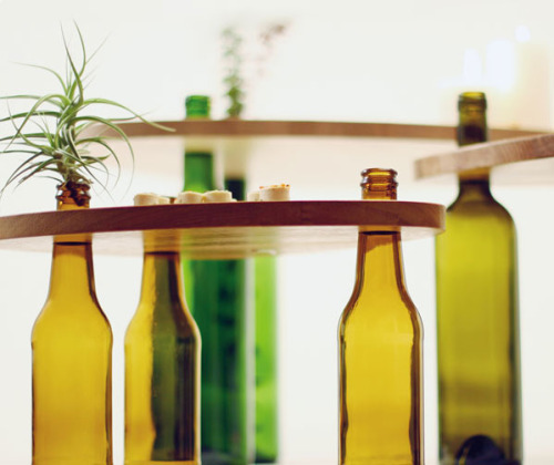 unconsumption:  Save wine bottles, make your own tables.  Simply insert bottles in to openings in pieces of wood. In addition to use as table tops, the pieces of wood (in this case, they're scrap wood sealed with a wax finish) can function as serving trays. Brazilian designer Tati Guimarães designed this collection. We featured her metal frame that holds corks — for use as trivets, or to hang on a wall — on Unconsumption here (way back in June 2009!). Check out her site, Ciclus, for additional information. See also: Earlier Unconsumption post on shelving made from wine bottles and pieces of wood. For other items in Unconsumption's wine o'clock series — an occasional series of posts highlighting examples of wine-related repurposing — browse here.