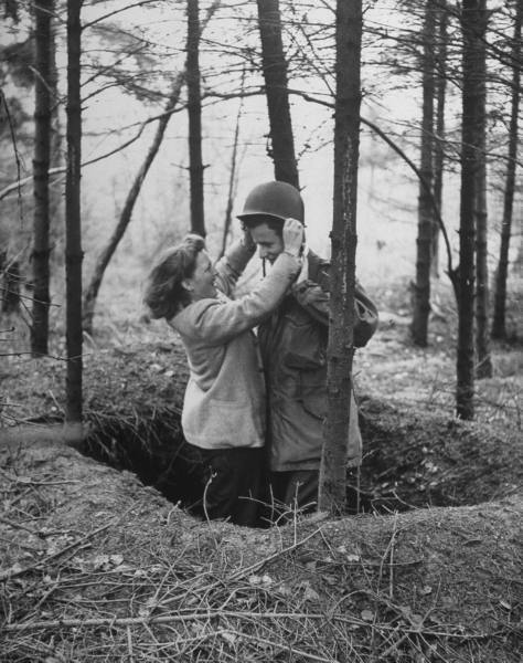 """Ex-Sgt. Ernie Kreiling gets helmet put on his head by his laughing wife in the foxhole where he first heard an enemy shell during their vacation tour of battlefields were he fought during WWII in North country."" April, 1947 (via LIFE)"