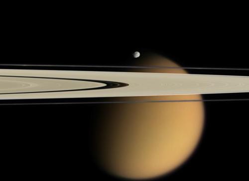 Titan Beyond the Rings   When orbiting Saturn, be sure to watch for breathtaking superpositions of moons and rings. One such picturesque vista was visible recently to the robot Cassini spacecraft now orbiting Saturn. In 2006 April, Cassini captured Saturn's A and F rings stretching in front of cloud-shrouded Titan. Near the rings and appearing just above Titan was Epimetheus, a moon which orbits just outside the F ring. The dark space in the A ring is called the Encke Gap, although several thin knotted ringlets and even the small moon Pan orbit there. Cassini and curious Earthlings await the coming Saturnian equinox this summer when the ring plane will point directly at the Sun. Mysterious spokes and telling shadows are expected to become visible that might give away more clues about the nature of Saturn's ring particles