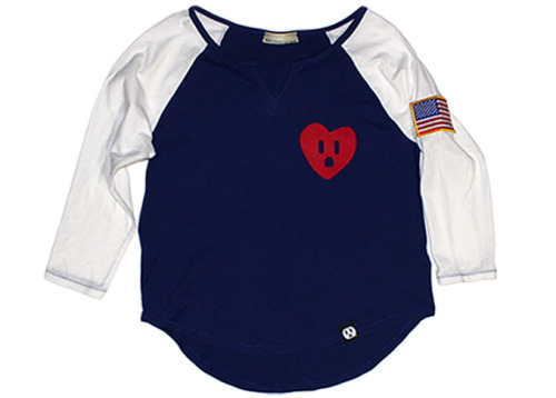 "The CdNMC Socket Heart Raglan 'USA' is now available! This women's exclusive garment from the Comme des Nouveau Marque Connexion™ by Fresh Connection Brand series is constructed in the USA using 100% imported cotton.  It features the CdNMC Socket Heart composed of plush red cotton fabric and an American Flag patch on the sleeve. Offering 3/4 raglan sleeves, a split neckline and a curved hemline, the CdNMC Socket Heart Raglan ""USA"" gives ladies a comfortable, quality, relaxed fitting garment for the spring season. It retails for $40USD and is available in limited quantities while supplies last. Available now on the FCB Webstore."