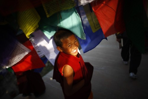 fotojournalismus:  A young Buddhist monk smiled as he took a break from performing a ritual at the Boudhanath Stupa temple in Katmandu, Nepal, on Dec. 27, 2012. Hundreds of monks from different monasteries prayed for peace and prosperity for the world. [Credit : Niranjan Shrestha/Associated Press]