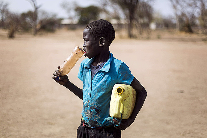 A South Sudanese kid carrying empty dirty jerrycane and plastic bottles is on his way to fetch water, in JanJang where is to open in March a new refugee camp to support the already overwhelmed Yida refugee camp in South Sudan on February 2, 2013. [Credit : Camille Lepage/AFP/Getty Images]