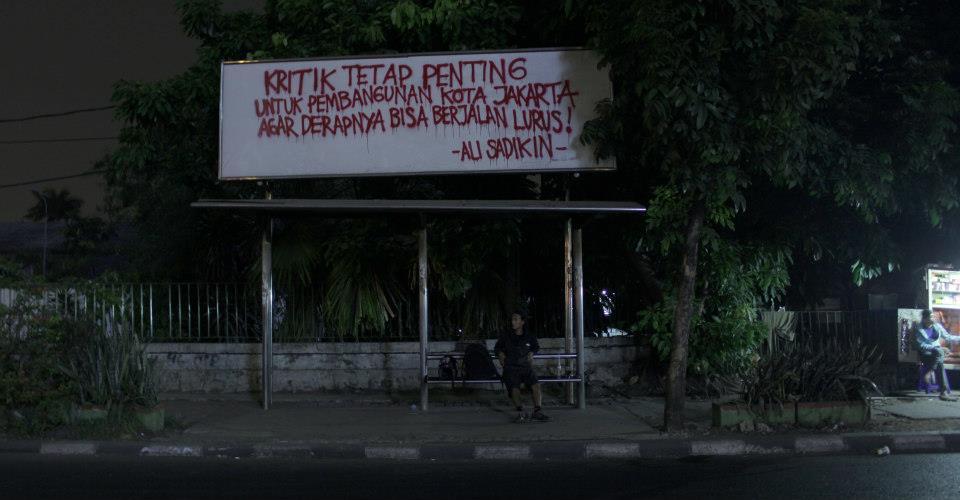 STREET ART PROTEST - OCCUPY BILLBOARD  Street artist: RHARHARHA Lokasi: Jakarta 2012  KRITIK TETAP PENTING UNTUK PEMBANGUNAN KOTA JAKARTA, AGAR DERAPNYA BISA BERJALAN LURUS! - ALI SADIKIN -