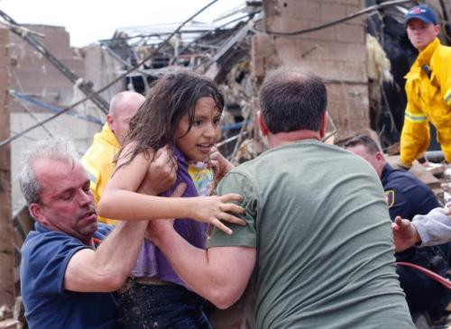 inothernews:  A child is pulled from the rubble of Plaza Towers Elementary School in Moore, a suburb of Oklahoma City.  The building had been leveled by a two-mile-wide tornado on Monday and several dozen children were thought to be among the casualties; the medical examiner has put the death toll at 37, with the figure expected to rise.  (Photo: Sue Ogrocki / AP via The New York Daily News)  Just awful.