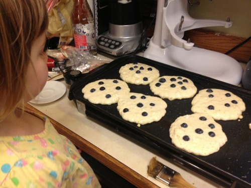 Greer is helping me make blueberry pancakes.