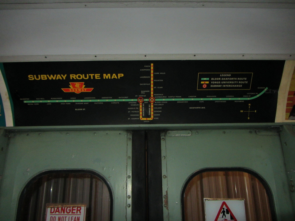 Historical Map: TTC Subway Route Map, c.1975–1977 While we're on the subject of the Toronto Subway map, here's a beautiful version from the mid-1970s. This particular map is in a preserved subway carriage at the Halton County Radial Railway museum, and shows the subway as it was before the Spadina extension was opened in 1978. This is actually probably my favourite version of this system's map: it has nice horizontal station labels alternating to either side of the route lines (although Finch station strangely breaks the pattern at the very top of the map), lovely even spacing between all the stations, and a very elegant curve at the eastern end of the Bloor-Danforth route. The interchange symbol is rather nice, too: a square within a circle that draws attention to it very well indeed. I'd steal this map to put on my wall over the modern version any day. Compare also to this map from 1966, when the Bloor-Danforth line first opened.   (Source: Sean_Marshall/Flickr)