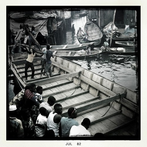 Residents of Makoko, a slum on stilts, work together to launch a newly built fishing boat into the water in July 2012 in Lagos, Nigeria. Photo by Jane Hahn @janehahn #nigeria #lagos #fishing #makoko #community #boats