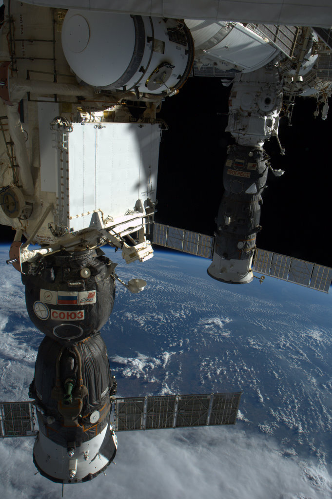 colchrishadfield:  Spaceships and Earth - foreground is the Soyuz we'll pilot home in May. Unmanned Progress vehicle in the background.