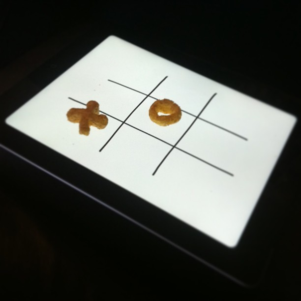 Noughts and crosses played with crisps on an iPad. We're in the future.