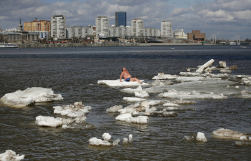 fotojournalismus:  Vladimir Samsonov, 59, sunbathes as he sits on an ice floe on the Yenisei River in Krasnoyarsk, Russia on April 26, 2013. [Credit : Ilya Naymushin/Reuters]