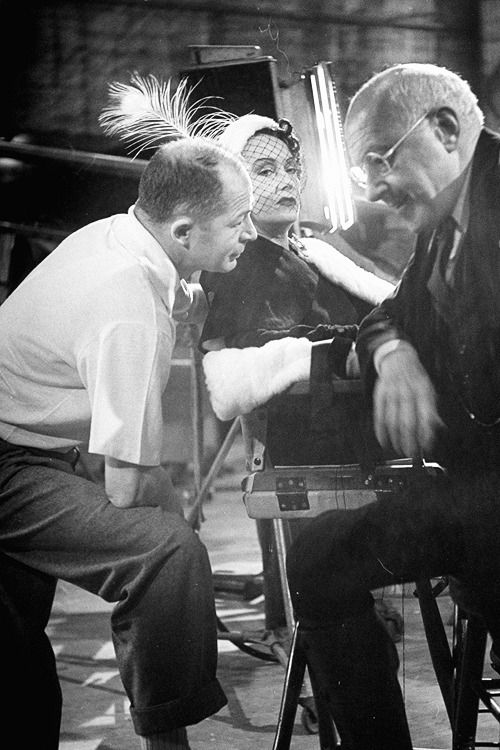 Director Billy Wilder talking with actress Gloria Swanson and Cecil B. DeMille during the shooting of the movie 'Sunset Blvd', photographed by Allan Grant, 1950.