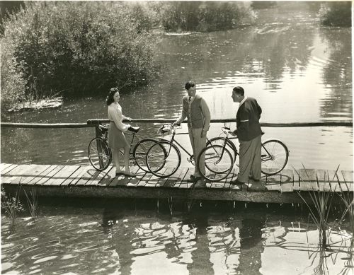 Linda Darnell, George Murphy and Jack Oakie walk bikes.
