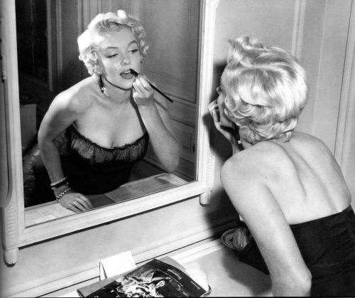 1954: Marilyn by Sam Shaw touching up her make-up before a press conference in New York for 'The Seven Year Itch'.