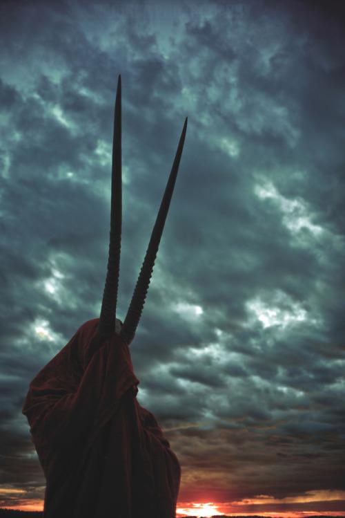 horns red robe sunset clouds dramatic sky melancholic melancholy beisa mourning rugged deity spirit shaman animal spirit ritual ancient fantasy mythical creatures photography photography art
