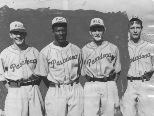 "Sharing this LAPL photo of Jackie Robinson with his Pasadena Jr. College teammates as today, MLB celebrates Jackie Robinson Day. Many Dodger fans know that Robinson broke baseball's color barrier (in Ebbets Field) on April 15, 1947. The movie 42 draws much-needed attention to this important achievement giving many the springboard to talk about Robinson's early life in Pasadena and at UCLA. Here's just a handful of articles: The Los Angeles Times shared a series of photos of Jackie Robinson through the years. For Zocalo Public Square, NPR's Scott Simon wrote about Jackie Robinson's days at UCLA (where he met his wife). Simon, ""Because of UCLA, [Robinson] had played sports at the major college level and excelled…He had learned how to cope with the questions and attentions of sportswriters…"" UCLA just unveiled a mural featuring Jackie Robinson at Jackie Robinson Stadium (more on KPCC). Several discussed how the film 42 brushed over Robinson's early history in Southern California. LA Weekly's Brendan Whalen wrote, ""Mostly, I'm disappointed because Robinson's journey really both starts and ends in Los Angeles."" For KCRW, Kevin Roderick spoke on Jackie Robinson's Pasadena life, ""Jackie Robinson, is through and through, a local story before he went on to play with the Brooklyn Dodgers."" Robinson's alma mater, Pasadena City College, celebrated with its own screening of 42 at Pasadena's ArcLight. African American reporter Wendell Smith covered Jackie Robinson for the African American-owned Pittsburgh Courier. Not allowed in the press box, Smith sat in the stands with a typewriter on his lap chronicling the achievements of Robinson. Bill Plaschke writes in the LA Times, ""Everyone will remember the headline, but few will remember the byline — Wendell Smith."" KPCC's Take Two interviewed Willie O'Ree, who broke the NHL's color barrier and also played hockey for the LA Blades. O'Ree recounted the 1962 NAACP luncheon held for Jackie Robinson in Los Angeles. According to the LA Times, Magic Johnson once said, ""If it wasn't for Jackie, then I wouldn't be able to own the Dodgers."" Both Johnson and MLB Commissioner Bud Selig hope to increase the number of black players in baseball. Magic Johnson, ""We have to bring the game to them. We have got to bring the kids to the [neighborhood] park, as young, young kids, to let them see how exciting it is to be a baseball player."""