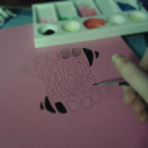 Painting the MAD FAMILY logo on the front of the world scrapbook~