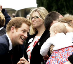 Prince Harry greets a baby during his visit to Tedworth House to officially open the charity's Tedworth House recovery centre on May 20, 2013.