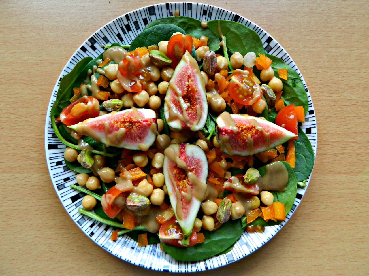 Spinach, orange bell pepper, cherry tomato, chickpea, pistachio and fig salad with a pomegranate molasses/tahini/orange juice dressing.