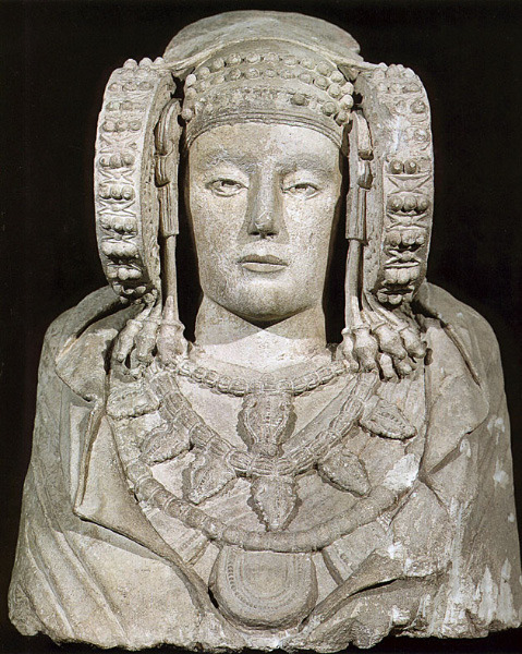 The Lady of Elche is beautiful stone bust of a woman that may have been used as a reliquary urn. It was discovered by a farmer in 1897 in near Valencia, Spain. She is now on display in the National Archaeological Museum of Spain in Madrid.   Believed to be dated to the 5th century BCE, the Lady of Elche is the symbol of Pre-Roman Iberian Archaeology.  Her face is found on virtually all Iberian prehistory textbook covers, and even on stuff as ordinary as postage stamps and banknotes.  Ironically, this iconic bust actually might be a forgery. Experts who believe this have given the following arguments: The Lady of Elche is the only one of its kind that is in the form of a bust.  All other Iberian statues from this time period, such as the Lady of Baza, are full bodied.  The amount of detail, particularly on the face and round headpieces are extraordinarily detailed compared to other Iberian statues with similar headdresses. Experts have found more similarities between the Lady of Elche and art nouveau/belle epoque aesthetics (which was popular at the time of discovery)  than with other Pre-Roman Iberian statues. The archaeological context of the bust is extremely lacking and shady. The reports have stated that the statue was found buried in loosely packed dirt, easily able to be buried and dug up. Coincidentally, the discovery of the Lady of Elche coincided with the arrival of Pierre Paris, an art collector from the Louvre, in Valencia, who purchased the statue for the Louvre collection days after the discovery.  Whether the Lady of Elche is a fake or not is still a mystery to this day, But her shady past has not stopped millions of tourists from flooding into Madrid every year to catch a glimpse of her.