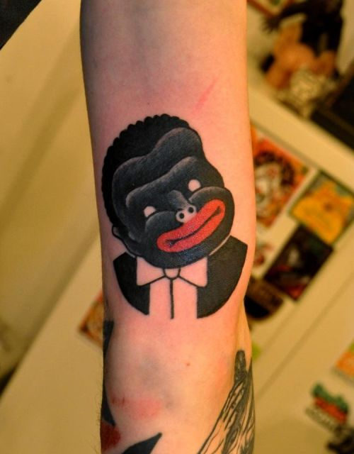 "I've talked before about racist tattoos and have often compared them to blackface. BUT I NEVER EXPECTED TO SEE AN ACTUAL BLACK FACE TATTOO. This disappointing image is by well-known Marcin Aleksander Surowiec. You can read more about blackface online, like here or here. Dehumanizing images like this, whether they intend to or not, help serve a much larger agenda: to perpetuate the myth that non-whites are non-human, an object that can be caricatured, or (in the case of war bonnets and, I would argue, black face) some/thing/ from a long time ago with no modern relevance. They subvert a long, rich, and diverse cultural history and help justify wage gaps, privatization of schools, mass incarceration, and healthcare inequalities people of color face the world over. I wanted to make sure everyone saw this tattoo because of how much ""post-racial"" discussion there seems to be going around the internet. Racism is alive and well in every part of our culture….."