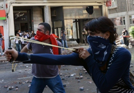 fuckyeahmarxismleninism:  A demonstrator uses a slingshot as clashes erupt between police and protesters during May Day celebrations in Istanbul, Turkey, May 1, 2013.