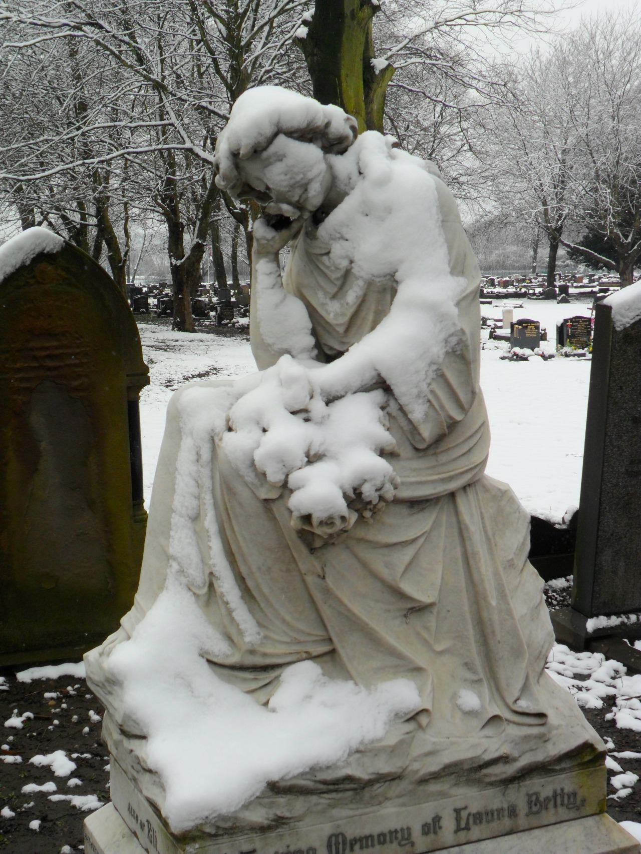 Sad snow covered Victorian grave statue, Tipton Cemetery, Tipton, West Midlands, England.